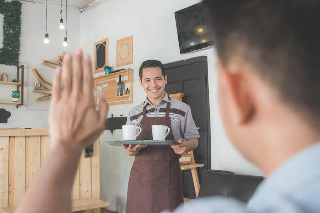 Männlicher kellner, der seinem kunden kaffee liefert
