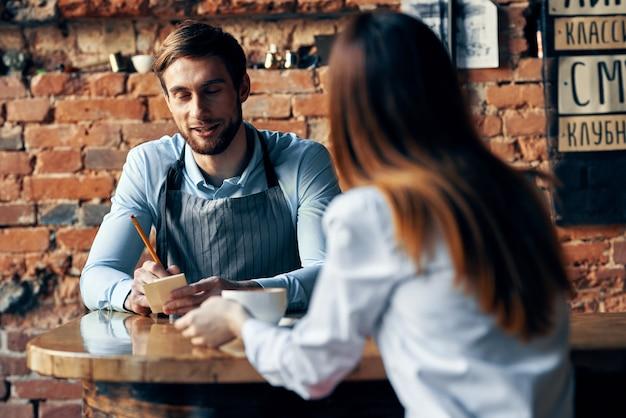 Männlicher kellner in grauen schürzen nimmt eine bestellung und eine tasse kaffee weibliche kunden an einem tisch in einem café
