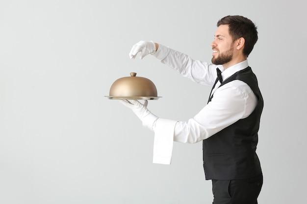 Männlicher kellner mit tablett und glocke auf grau