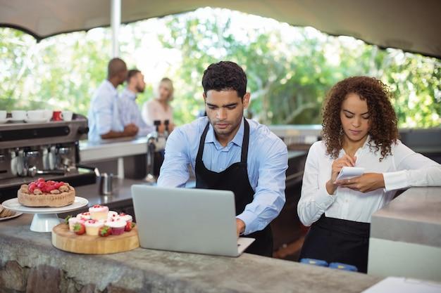 Männlicher kellner und weibliche kellnerin mit laptop