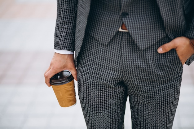 Männlicher klagenabschluß, der oben in der hand kaffee hält