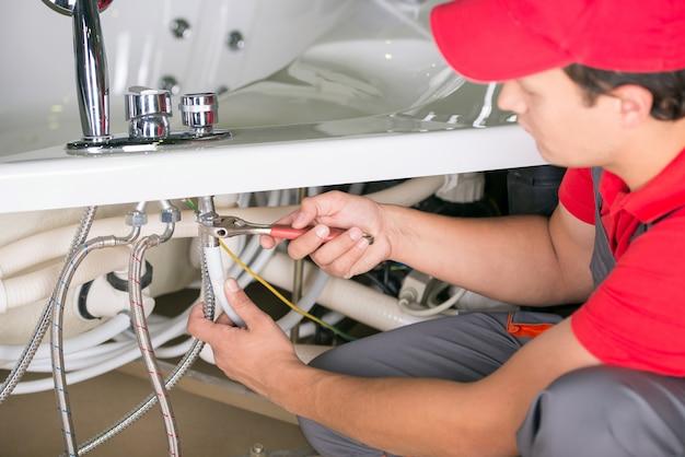 Männlicher klempner, der abflussrohr im badezimmer repariert.