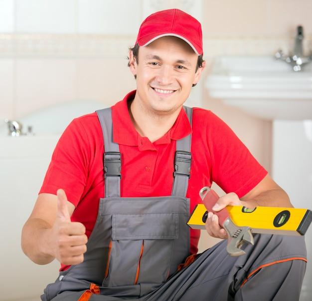 Männlicher klempner, der sich daumen zeigt und werkzeug hält.