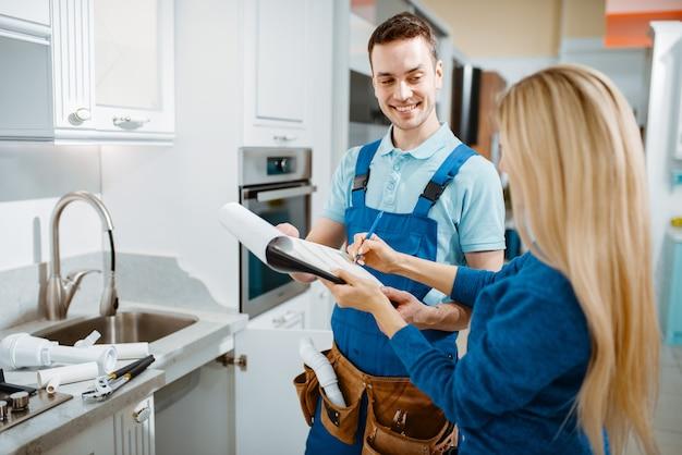 Männlicher klempner in uniform und weiblicher kunde in der küche. handwerker mit werkzeugtaschen-reparaturspüle, sanitäranlagen-service zu hause