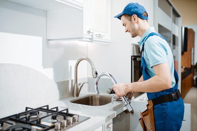 Männlicher klempner in uniform wechselt wasserhahn in der küche. handwerker mit werkzeugbeutel reparaturspüle, sanitär-service zu hause