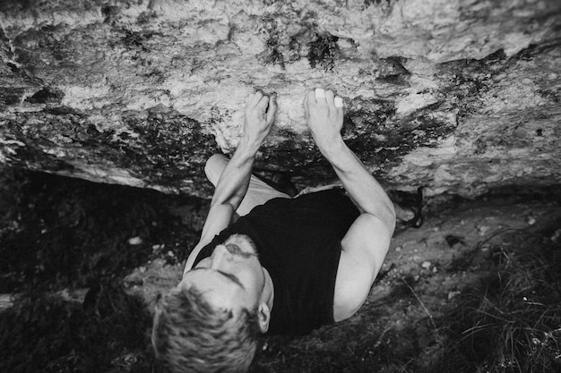 Männlicher kletterer, der an der klippe b & w hängt
