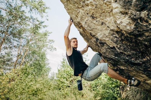 Männlicher kletterer, der an der klippe hängt