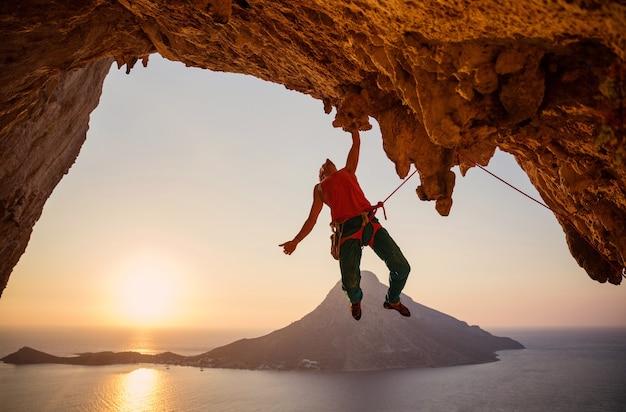 Männlicher kletterer, der an klippe mit einer hand bei sonnenuntergang hängt. kalymnos insel, griechenland.