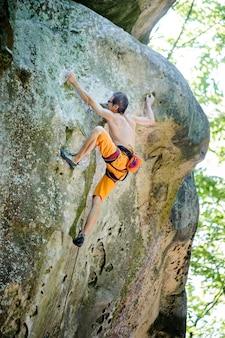 Männlicher kletterer, der mit seil auf einer felsigen wand klettert