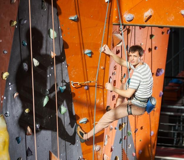 Männlicher kletterer übend, auf felsenwand zuhause kletternd