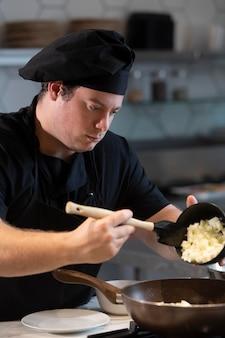 Männlicher koch beim küchenkochen