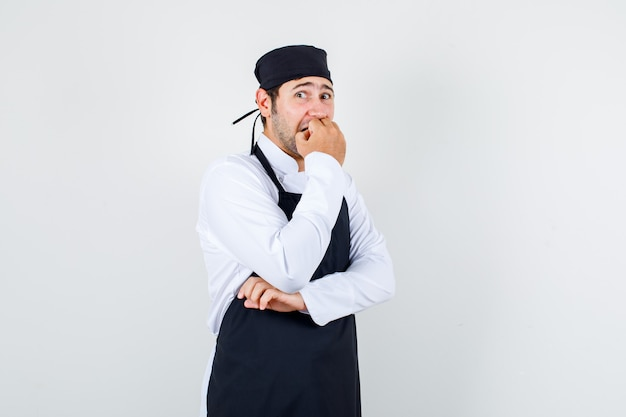Männlicher koch beißt seine nägel in uniform, schürze und sieht stressig aus, vorderansicht.