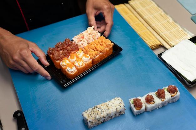 Männlicher koch bereitet eine sushi-bestellung zum mitnehmen vor