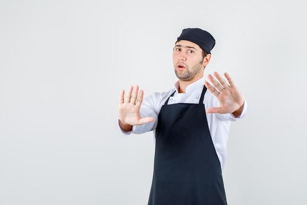 Männlicher koch, der ablehnungsgeste in uniform, schürze zeigt und ernsthafte vorderansicht sieht.