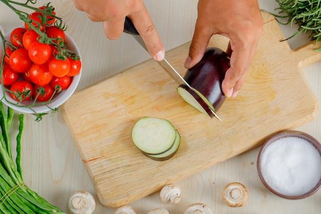 Männlicher koch, der aubergine auf holzbrett in der küche hackt