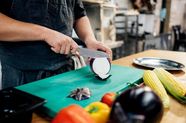 Männlicher koch, der aubergine in der küche schneidet