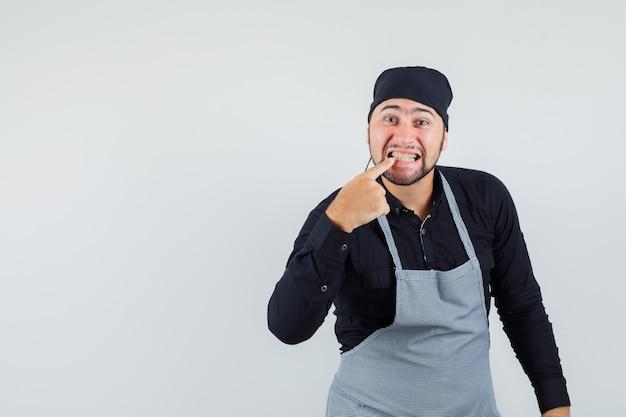 Männlicher koch, der auf seine zähne in hemd, schürze, vorderansicht zeigt.