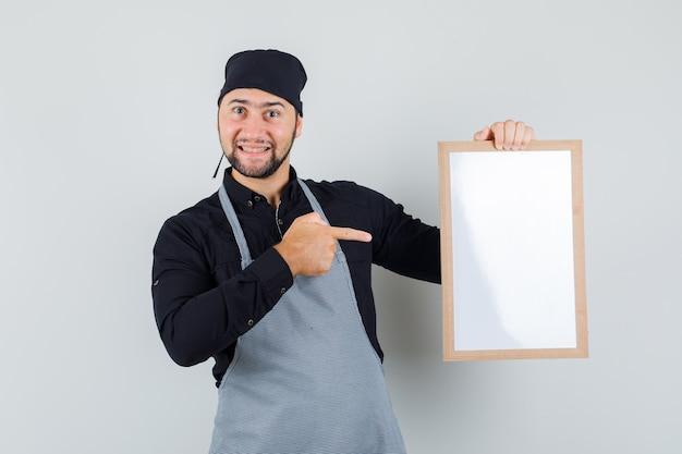Männlicher koch, der auf weiße tafel im hemd, in der schürze zeigt und glücklich schaut, vorderansicht.