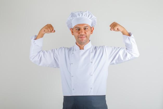 Männlicher koch, der beugende muskeln zeigt und in uniform, schürze und hut weglächelt und selbstbewusst aussieht