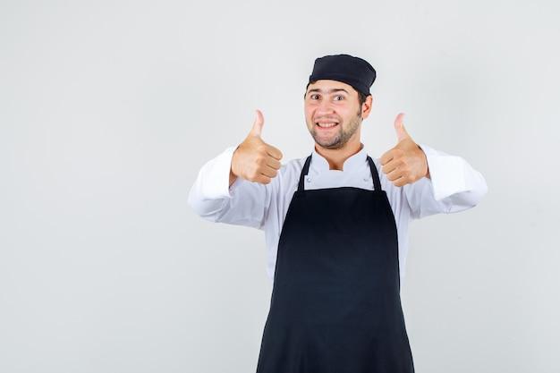Männlicher koch, der daumen in uniform, schürze zeigt und glücklich schaut. vorderansicht.