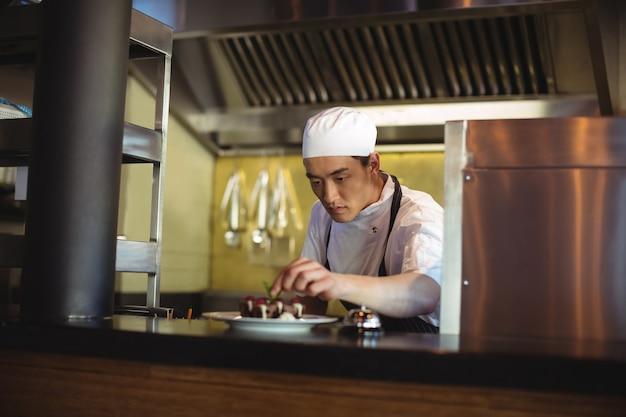 Männlicher koch, der dessertteller garniert