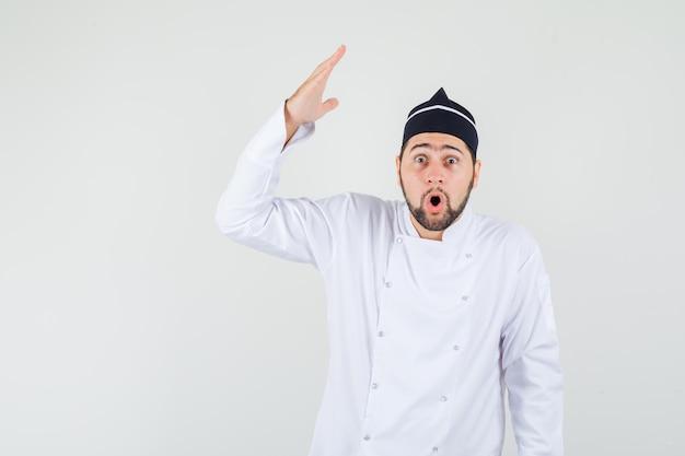 Männlicher koch, der die hand mit offener handfläche in weißer uniform anhebt und überrascht aussieht. vorderansicht.
