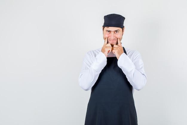Männlicher koch, der ein lächeln auf gesicht in uniform, schürze erzwingt und düster aussieht. vorderansicht.