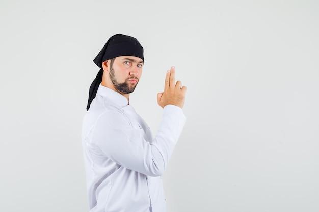 Männlicher koch, der eine schießgeste in weißer uniform zeigt und streng aussieht.