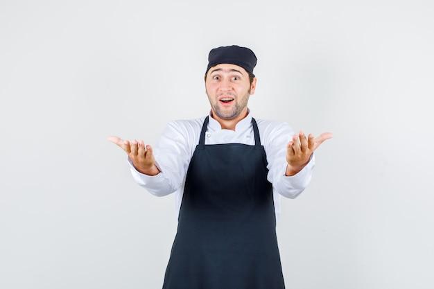 Männlicher koch, der einlädt, mit händen in uniform, schürze zu kommen und erstaunt auszusehen. vorderansicht.