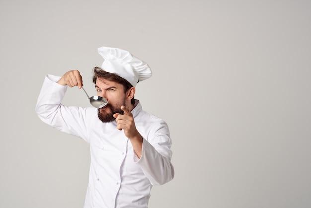 Männlicher koch, der essen in der küche verkostet