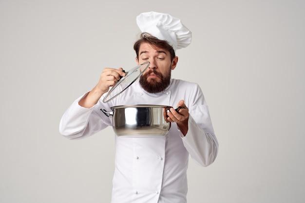 Männlicher koch, der essen in einem kochtopf-küchenprofi zubereitet