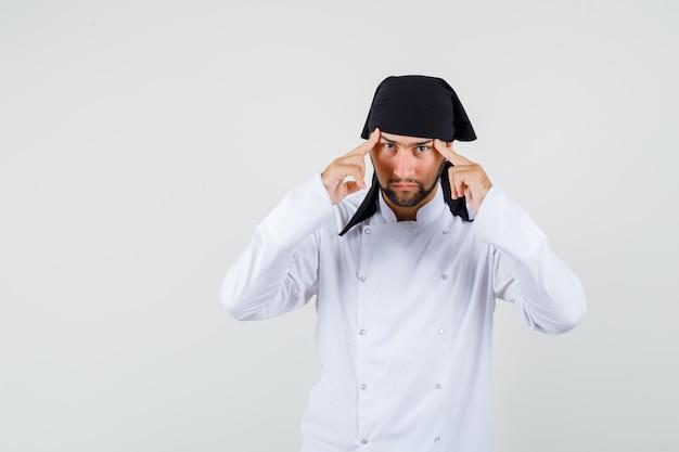 Männlicher koch, der finger an den schläfen in weißer uniform hält und ernst aussieht, vorderansicht.