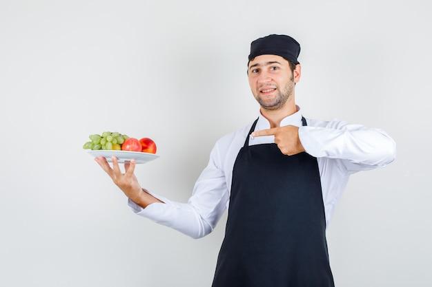 Männlicher koch, der finger auf früchte im teller in uniform, schürze zeigt und fröhlich schaut. vorderansicht.