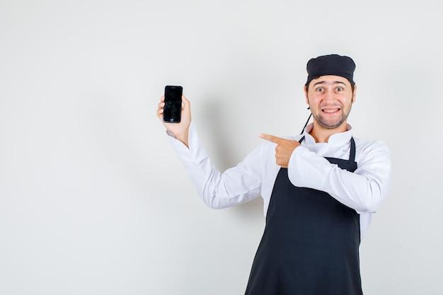 Männlicher koch, der finger auf handy in uniform, schürze und fröhlich aussehend zeigt. vorderansicht.
