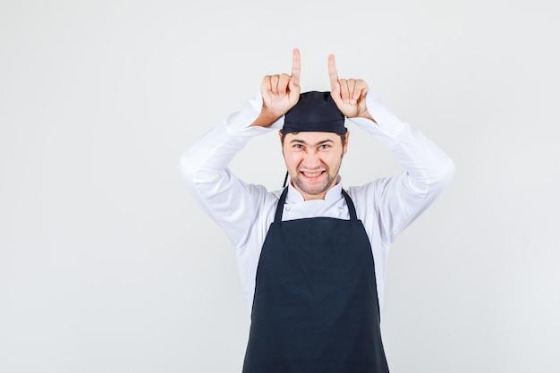 Männlicher koch, der finger auf kopf wie hörner in uniform, schürze hält und lustig aussieht. vorderansicht.