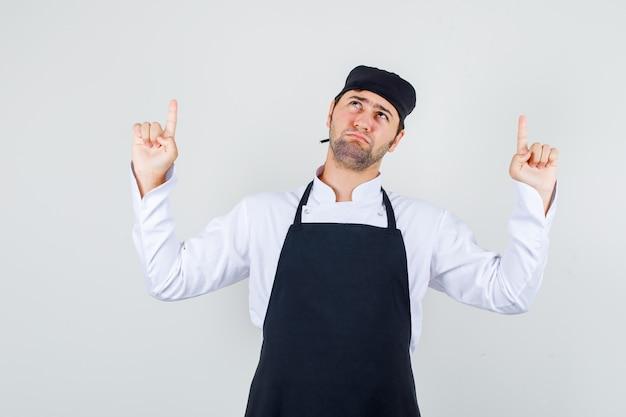 Männlicher koch, der finger in uniform, schürze zeigt und düster, vorderansicht schaut.