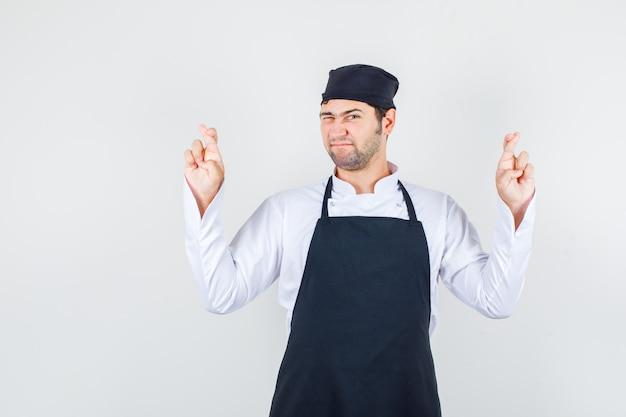 Männlicher koch, der finger mit blinzelndem auge in uniform, schürze, vorderansicht kreuzt.