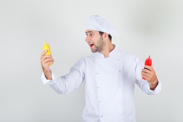 Männlicher koch, der flaschen ketchup und senf in der weißen uniform hält