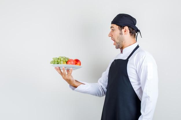 Männlicher koch, der früchte im teller in uniform, schürze hält und erstaunt schaut. vorderansicht.