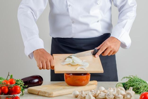 Männlicher koch, der gehackte zwiebeln in schüssel in uniform und schürze in küche gießt