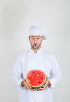 Männlicher koch, der geschnittene wassermelone in der weißen uniform hält
