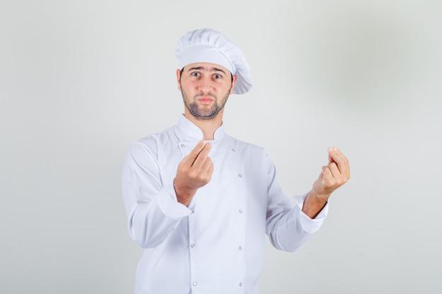Männlicher koch, der geste mit händen in der weißen uniform zeigt und verwirrt schaut