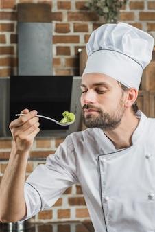 Männlicher koch, der grünen brokkoli im löffel riecht
