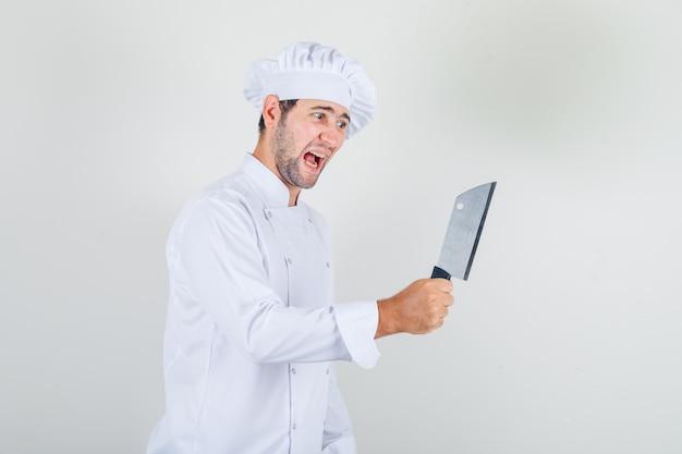 Männlicher koch, der hackbeil in der weißen uniform hält und aggressiv aussieht.
