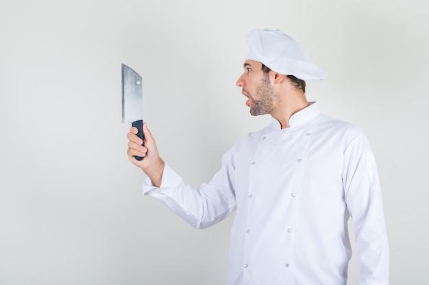 Männlicher koch, der hackmesser in der weißen uniform hält und schockiert aussieht