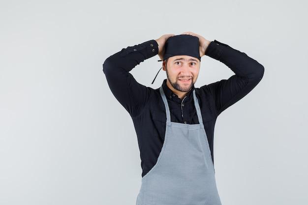 Männlicher koch, der hände auf kopf in hemd, schürze hält und niedlich, vorderansicht schaut.