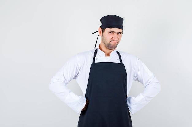 Männlicher koch, der hände auf taille hält, während er in uniform, schürze finster blickt und unzufrieden aussieht. vorderansicht.