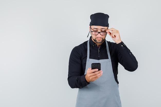 Männlicher koch, der handy durch brille in hemd, schürze betrachtet und beschäftigt schaut. vorderansicht.