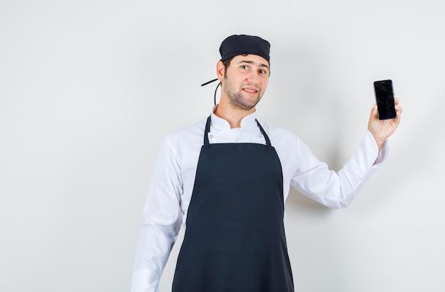 Männlicher koch, der handy in uniform, schürze hält und optimistisch schaut. vorderansicht.