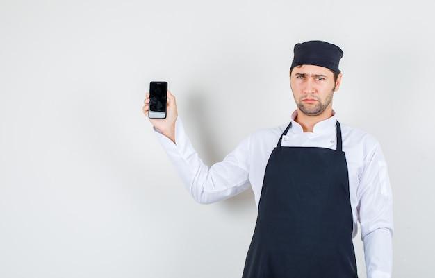 Männlicher koch, der handy in uniform, schürze hält und verärgert, vorderansicht schaut.
